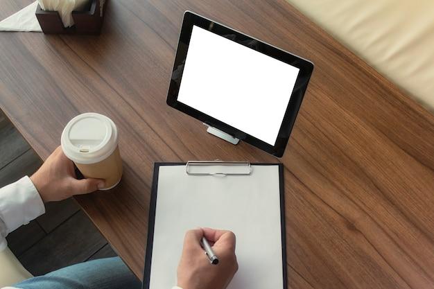 Geschäftsmann in einem weißen hemd mit einem digitalen tablett in seinen händen unterschreibt einen vertrag im büro. arbeitsplatz mit einer tasse kaffee und einem dokument mit einem stift auf einem holztisch.