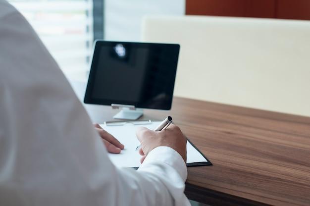 Geschäftsmann in einem weißen hemd mit einem stift in seinen händen unterschreibt einen vertrag im büro