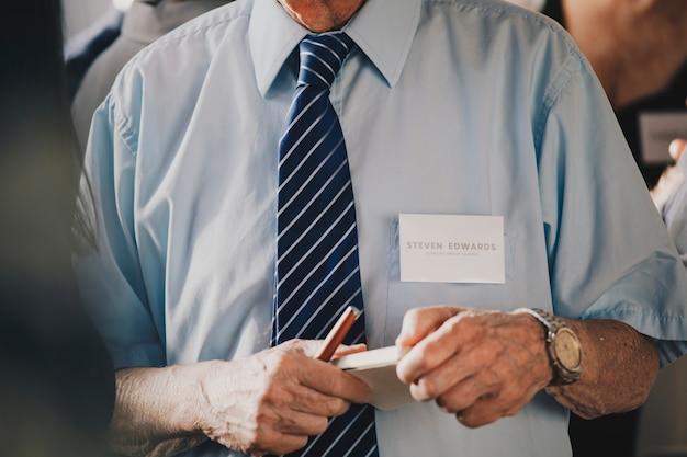 Geschäftsmann in einer besprechung, die ein notizbuch und einen stift hält