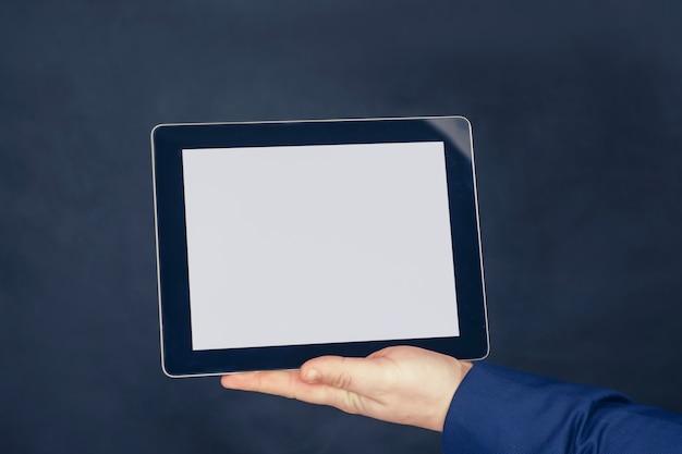 Geschäftsmann in einer blauen jacke hält ein modell eines tablets mit einem weißen bildschirm auf dunklem hintergrund.