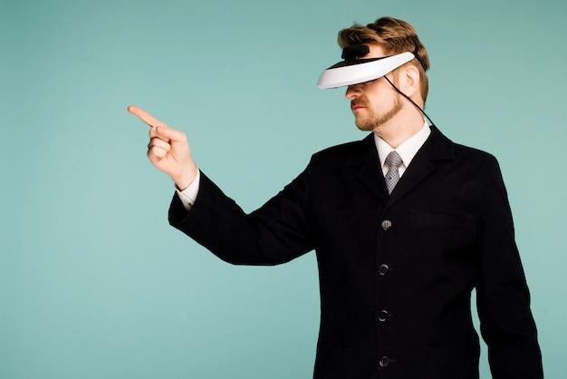 Geschäftsmann in einer formellen kleidung, die eine brille der virtuellen realität trägt, zeigt finger weg