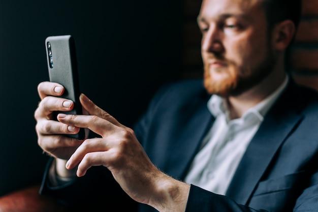 Geschäftsmann in einer klage, die in einem stuhl mit einem smartphone sitzt und auf der videoverbindung spricht.