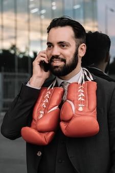 Geschäftsmann in einer klage sprechend an seinem handy mit den roten boxhandschuhen, die von seinem halslehnen hängen
