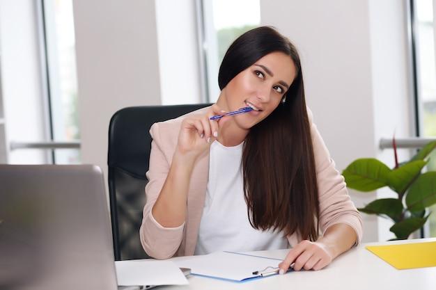 Geschäftsmann in einer rosa jacke, die an einem laptop im büro sitzt.