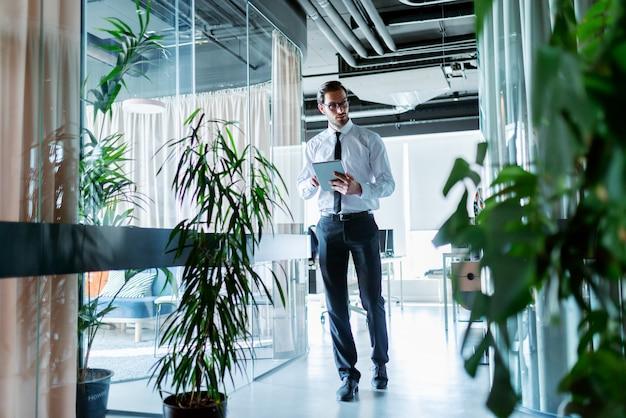 Geschäftsmann in formeller kleidung, der den flur entlang geht und tablette für arbeit verwendet.