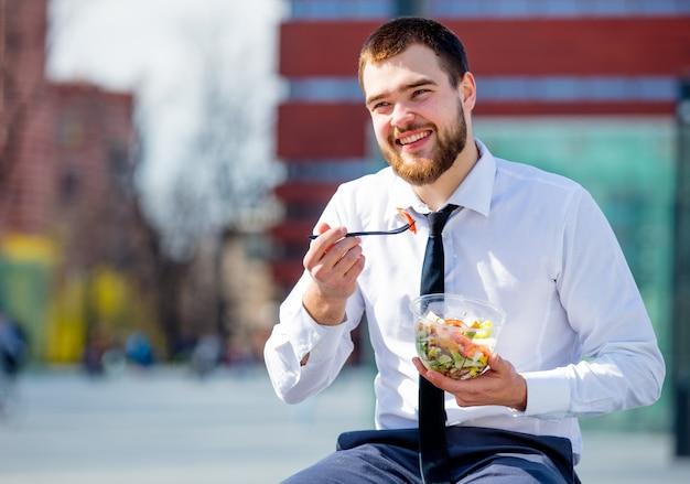 Geschäftsmann in hemd und krawatte mit salat lunchbox