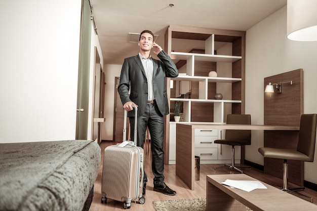Geschäftsmann in schuhen. junger geschäftsmann, der dunklen anzug und lederschuhe trägt, die im hotelzimmer stehen