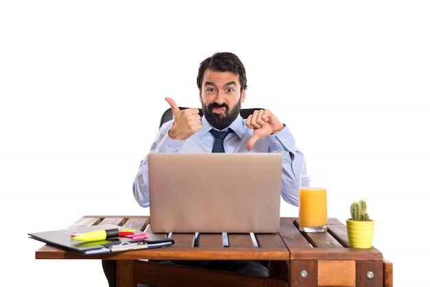 Geschäftsmann in seinem büro macht gut-schlechtes zeichen