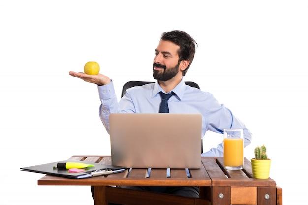Geschäftsmann in seinem büro mit einem apfel