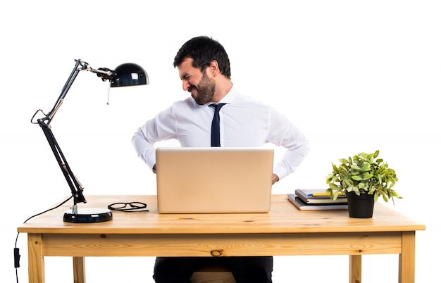 Geschäftsmann in seinem büro mit rückenschmerzen