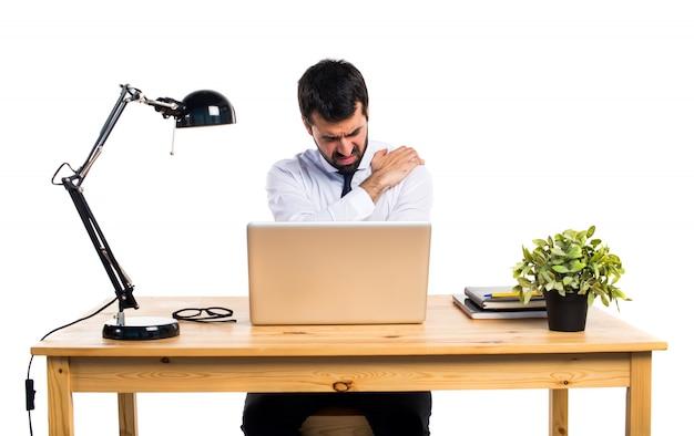 Geschäftsmann in seinem büro mit schulterschmerzen