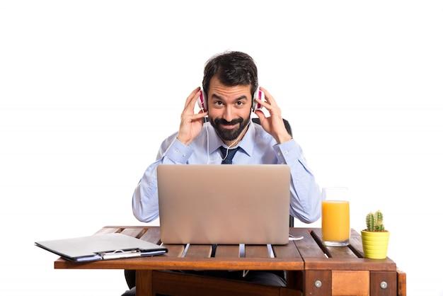 Geschäftsmann in seinem büro musik hören