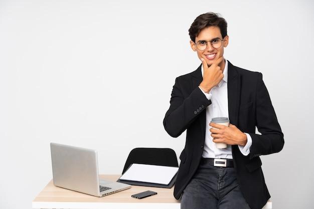 Geschäftsmann in seinem büro über dem weißen wandlachen