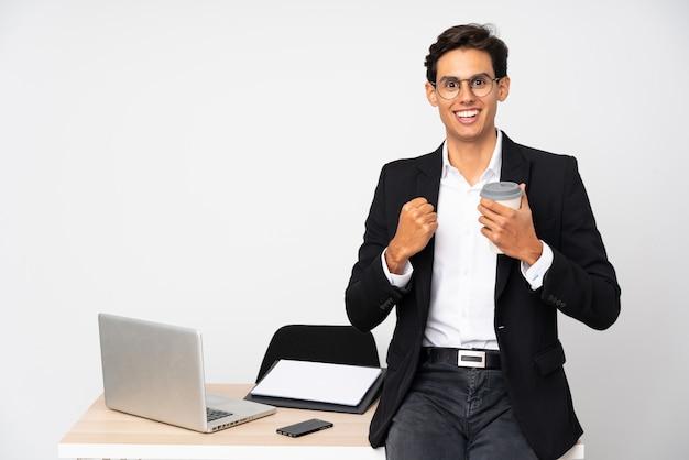 Geschäftsmann in seinem büro über der lokalisierten weißen wand, die einen sieg feiert