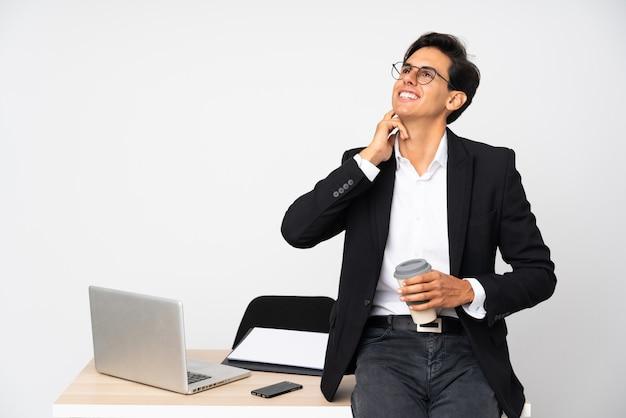 Geschäftsmann in seinem büro über isolierte weiße wand, die eine idee denkt