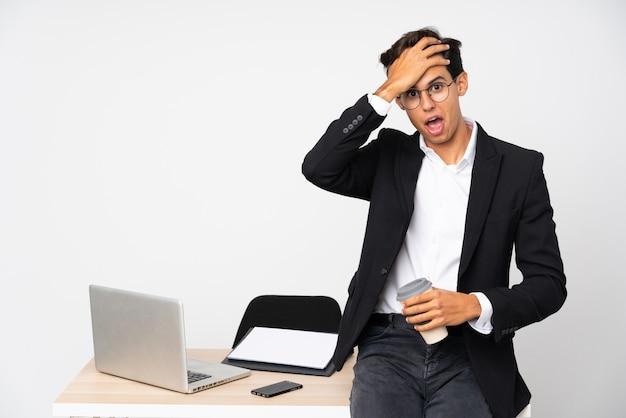 Geschäftsmann in seinem büro über weißer wand mit überraschungsgesichtsausdruck