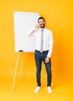 Geschäftsmann in voller länge, der eine darstellung auf weißem brett über der lokalisierten gelben wand macht telefongeste gibt. rufen sie mich zurück zu unterzeichnen