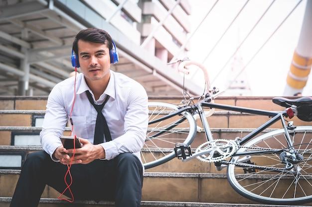 Geschäftsmann ist entspannend musik mit seinem fahrrad auf der seite hören