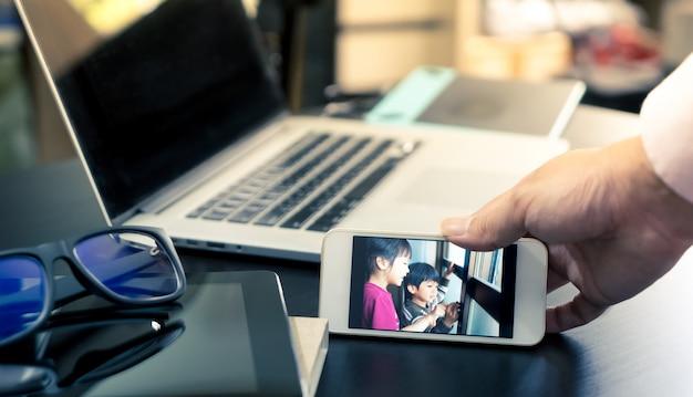 Geschäftsmann ist videoanruffamilie auf smartphone für motivation