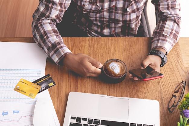 Geschäftsmann kaffee trinken und mit telefon am schreibtisch
