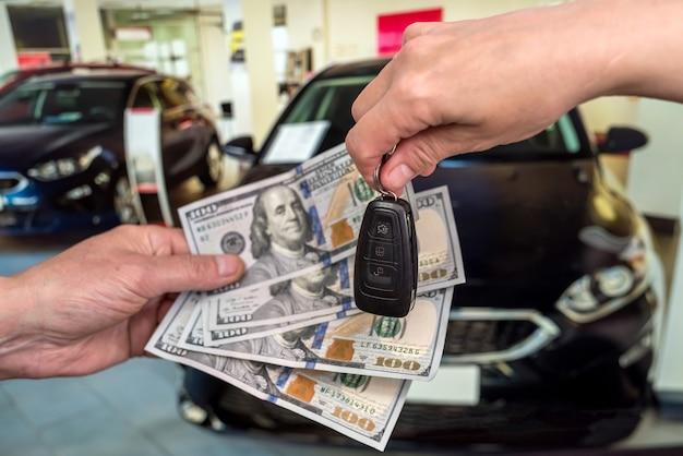 Geschäftsmann kauft neues auto im ausstellungsraum, gibt dollar geld und nimmt schlüssel vom auto, finanzkonzept