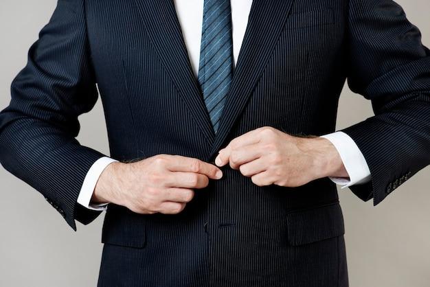 Geschäftsmann knöpft seinen anzug zu