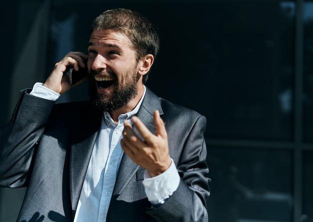 Geschäftsmann kommuniziert am telefon im freien