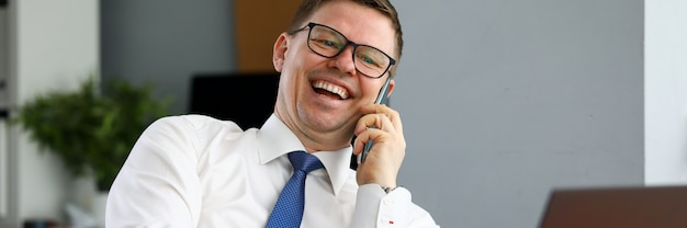 Geschäftsmann lachend am telefon mit partner sprechend