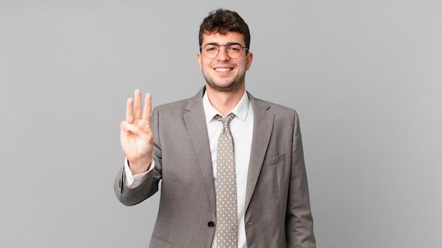 Geschäftsmann lächelnd und freundlich aussehend, nummer drei oder dritte mit der hand nach vorne zeigend, herunterzählen