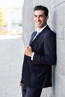Geschäftsmann lehnt an einer wand lächelnd