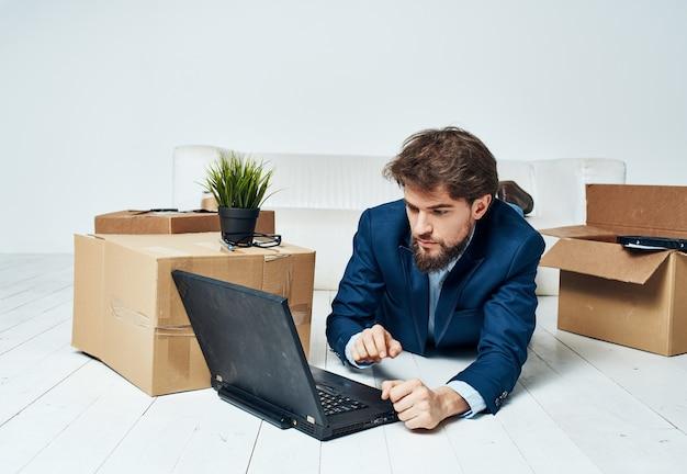 Geschäftsmann liegt auf dem boden vor einem laptop, arbeitet ohne ausgepackte sachen