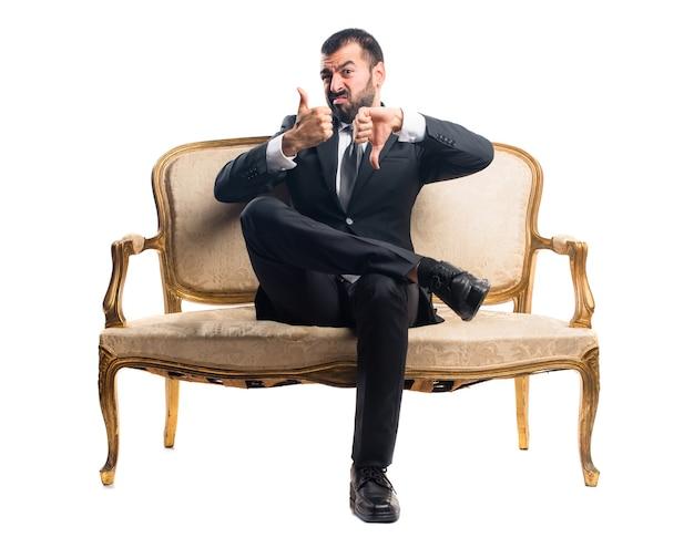Geschäftsmann macht gut-schlechtes zeichen