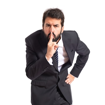 Geschäftsmann macht stille geste über isolierten weißen hintergrund