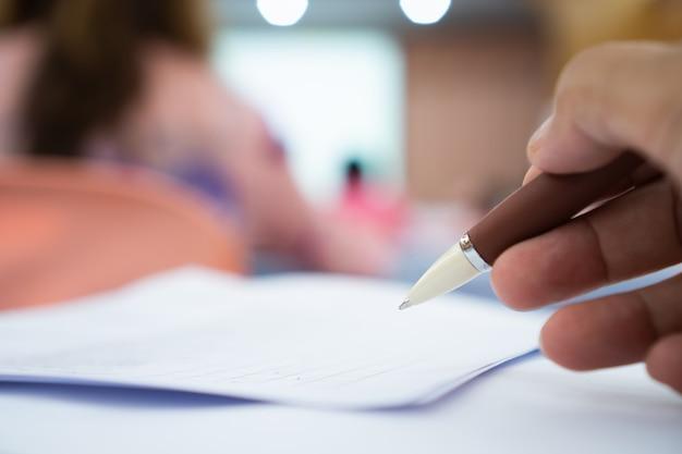 Geschäftsmann-manager, der bewerberfüllungsdokumente überprüft und unterzeichnet, dokumentiert papierfirma