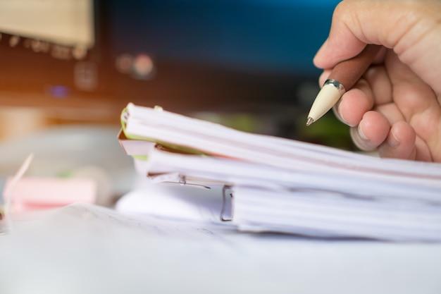 Geschäftsmann manager, der dokumentenberichte überprüft und unterzeichnet