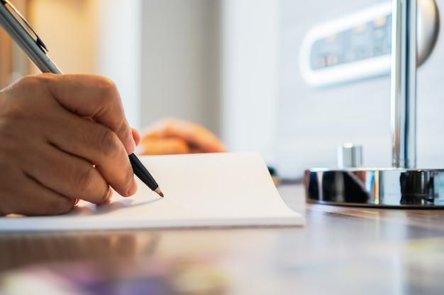 Geschäftsmann-manager, der stift für das unterzeichnen von dokumenten sitzt