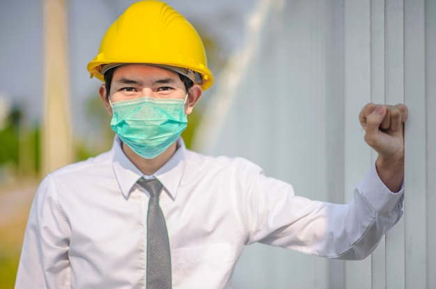 Geschäftsmann-manager verwenden gesichtsmaske gelber schutzhelm, der blaupausenarbeitsbaukonstruktion hält