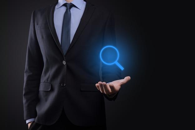 Geschäftsmann, mann halten in der hand lupensymbol. geschäfts-, technologie- und internetkonzept