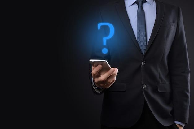 Geschäftsmann mann hand halten schnittstelle fragezeichen zeichen web. fragen online stellen, faq-konzept, was wo wann wie und warum, informationen im internet suchen.