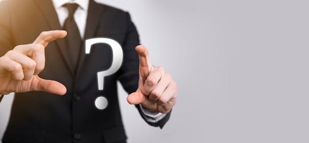 Geschäftsmann mann hand halten schnittstelle fragezeichen zeichen web. fragen online stellen, faq-konzept, was wo wann wie und warum, informationen im internet suchen