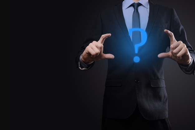 Geschäftsmann mann hand halten schnittstelle fragezeichen zeichen web. fragen sie online, faq-konzept, was wo wann wie und warum, suchen sie informationen im internet.