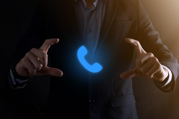 Geschäftsmann mann im anzug auf schwarzem hintergrund halten telefonsymbol jetzt anrufen business communication support center kundendienst-technologiekonzept
