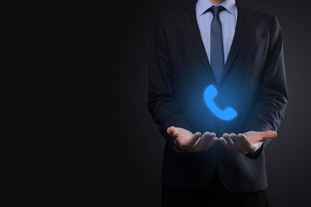 Geschäftsmann mann im anzug auf schwarzem hintergrund halten telefonsymbol. rufen sie jetzt business communication support center kundendienst-technologie-konzept an.