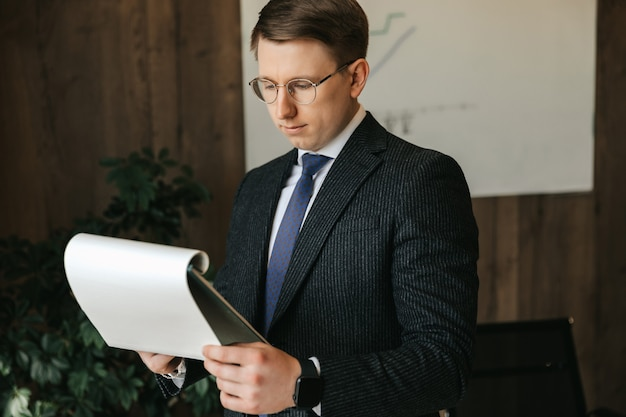 Geschäftsmann mann in brille untersucht dokumente im büro.