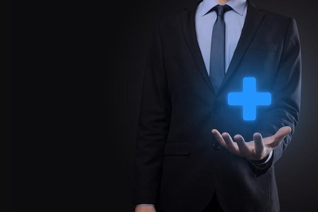 Geschäftsmann, mann in der hand bieten positive dinge wie gewinn, nutzen, entwicklung, csr durch pluszeichen dargestellt