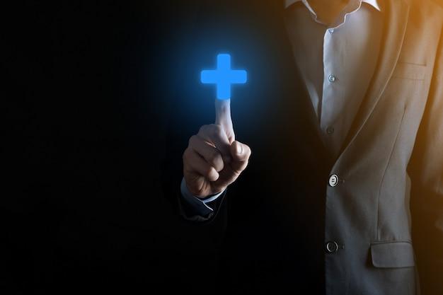 Geschäftsmann, mann in der hand halten bieten positive dinge wie gewinn, nutzen, entwicklung, csr durch pluszeichen dargestellt. die hand zeigt das pluszeichen.