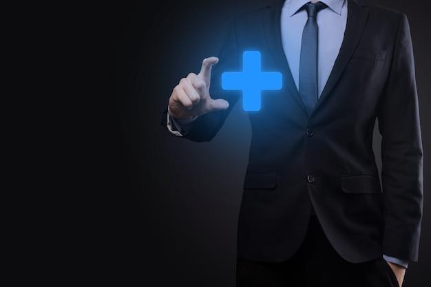 Geschäftsmann, mann in der hand halten bieten positive dinge wie gewinn, vorteile, entwicklung, csr, dargestellt durch pluszeichen. die hand zeigt das pluszeichen.