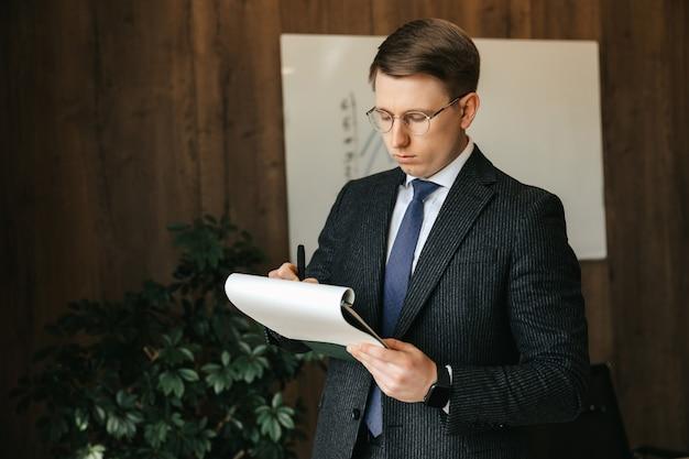 Geschäftsmann mann in gläsern, schreibt den papierkram im büro auf.