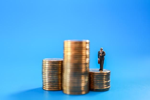 Geschäftsmann-miniaturmenschenfigur mit handtasche, die auf münzen schaut, um zu beobachten