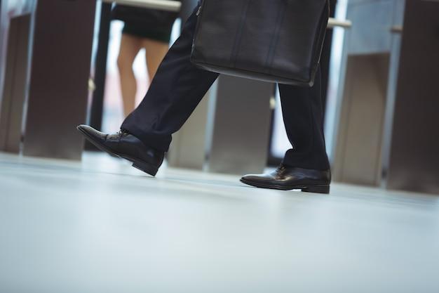 Geschäftsmann mit aktentasche, die im büro geht